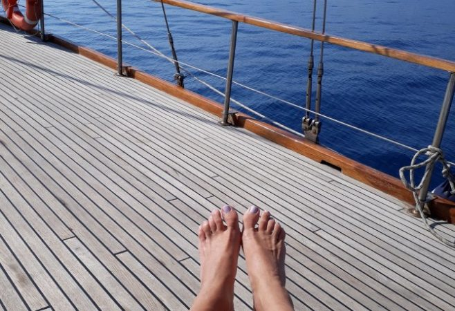 Füße barfuß am Segelschiff dahinter blaues Meer